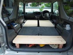 その上に幅45センチ・長さ90センチ・厚さ9ミリのベニヤ板を2枚、怪我をしないように角を丸めたやつを敷いて、これでほぼフラットな場所が完成。